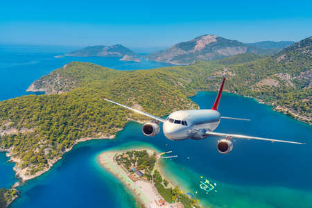 Airplane is flying over amazing mountains with forest and sea at sunrise in summer. Landscape with white passenger airplane, sky, islands and blue water. Passenger aircraft. Travel and resort. Tourism Stock Photo