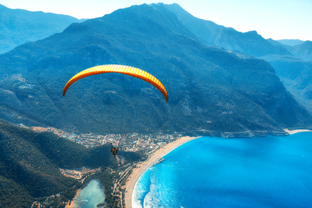Paragliding in the sky. Paraglider tandem flying over the sea with blue water and mountains in bright sunny day. Aerial view of paraglider in Oludeniz, Turkey. Extreme sport. Landscape Stock Photo
