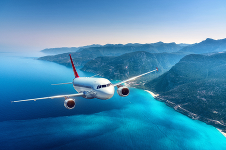 Airplane is flying over islands and sea at sunrise in summer. Landscape with white passenger airplane, seashore, mountains, sky, and blue water. White passenger aircraft. Travel and resort. Tourism