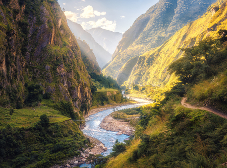 Colorful landscape with high Himalayan mountains, beautiful curving river, green forest, blue sky with clouds and yellow sunlight at sunset in summer in Nepal. Mountain valley. Travel in Himalayas