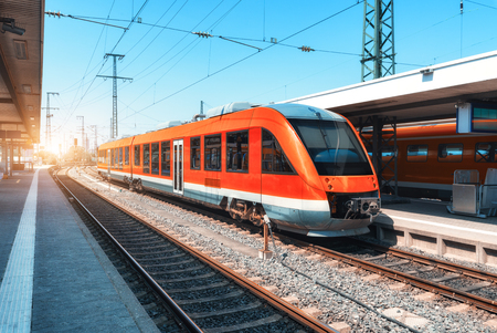High speed red train on the railway station at sunset in summer. Modern commuter train on the railway platform. Industrial scene with railroad. Passenger transportation. intercity vehicle. Travel