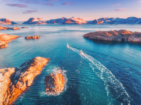 Aerial view of fishing boats, rocks in the blue sea, snowy mountains and colorful purple sky with red clouds at sunset in winter in Lofoten islands, Norway, Landscape with two ship. Top view. Travel
