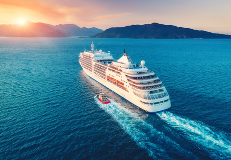 Cruise ship at harbor. Aerial view of beautiful large white ship at sunset. Colorful landscape with boats in marina bay, sea, colorful sky. Top view from drone of yacht. Luxury cruise. Floating liner 스톡 콘텐츠