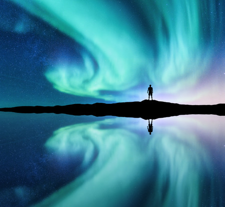 Northern lights and silhouette of standing man in the hill in Norway. Aurora borealis and man. Stars and green polar lights. Night landscape with aurora, lake, sky reflection in water. Travel. Concept 免版税图像