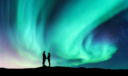Northern lights and hugging couple on the hill. Landscape with night starry sky, aurora borealis, silhouette of man and woman. People. Concept background with Lovers and polar lights. Nature. Travel