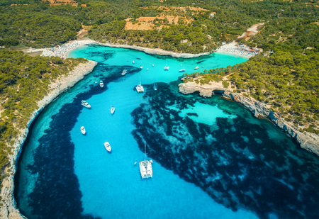Aerial view of boats, luxury yachts and transparent sea at sunny day in Mallorca, Spain. Colorful summer landscape with marina bay, blue water, sandy beach, sky. Balearic islands. Top view. Travel