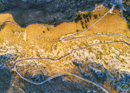 Aerial view of mountain curve road with cars, green forest at sunset in summer in Europe. Landscape with asphalt road, trees on the rocks. Highway through the park. Top view from flying drone. Nature
