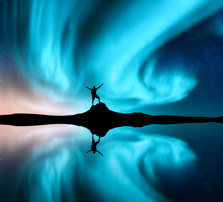 Northern lights and silhouette of standing man with raised up arms on the stone. Norway. Night landscape with aurora borealis, happy man, sea, reflection in water, starry sky, polar lights. Aurora