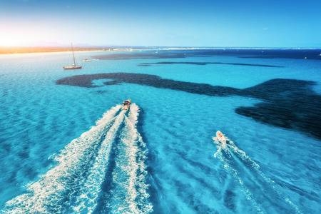 Speed motorboats on the seashore in Mallorca, Spain. Aerial view of floating boat on the transparent blue sea at sunset. Summer travel. Top view. Seascape with yacht in motion in bay. Travel in Europe