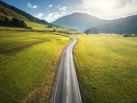 Aerial view of the road in mountain valley in Dolomites, Italy. Top view of perfect asphalt roadway, meadows with green grass, hills in autumn. Highway through the fields. Trip in europe. Travel
