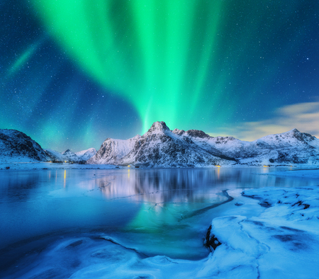 Aurora borealis over snowy mountains, frozen sea coast and reflection in water in Lofoten islands, Norway. Northern lights. Winter landscape with polar lights, ice in water. Starry sky with aurora Фото со стока
