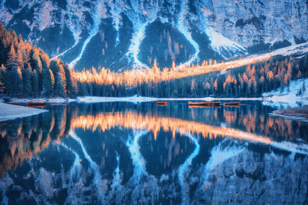 Braies lake with beautiful reflection in water at sunrise in autumn in Dolomites, Italy. Landscape with forest, mountains, boats on the lake, water, trees with colorful foliage. Italian alps. Nature Stock Photo