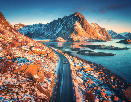 Aerial view of beautiful mountain road near the sea, mountains, purple sky at sunset in Lofoten islands, Norway in winter. Top view of road, car, high snowy rocks with stones, coastline, blue water