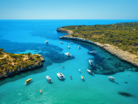 Aerial view of boats, luxury yachts, green trees and transparent sea in sunny bright day in Mallorca, Spain. Summer landscape with bay, azure water, beach, blue sky. Balearic islands. Top view. Travel Stockfoto