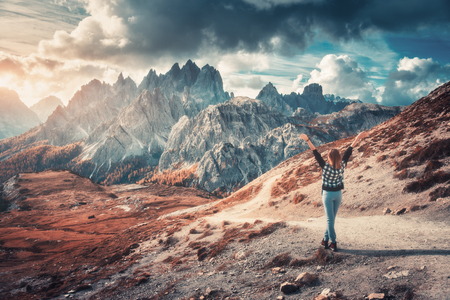 Young woman with raised up arms and high mountains at sunset in autumn in Dolomites, Italy. Landscape with happy girl, dramatic sky with clouds, orange trees, high rocks in italian alps in fall Banco de Imagens