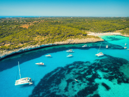 Aerial view of boats, luxury yachts, green trees and transparent sea in sunny bright day in Mallorca, Spain. Summer landscape with bay, azure water, beach, blue sky. Balearic islands. Top view. Travel 版權商用圖片