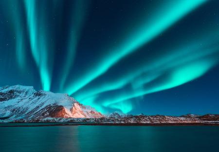 Aurora borealis powyżej góry pokryte śniegiem na Lofotach, Norwegia. Zorza polarna w zimie. Nocny krajobraz z polarnymi światłami, ośnieżonymi skałami, odbicie w morzu. Gwiaździste niebo z zorzą polarną Zdjęcie Seryjne