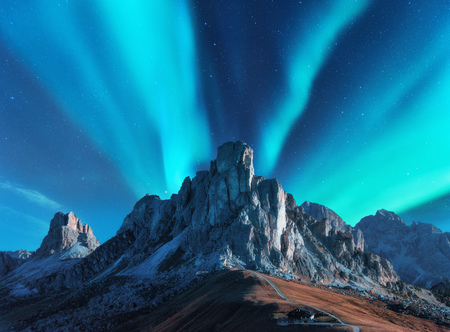 Northern lights above mountains at night in Europe. Aurora borealis. Starry sky with polar lights and high rocks. Beautiful landscape with aurora, road, buildings on the hill, mountain ridge. Travel
