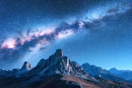 Via Lattea sopra le montagne di notte in autunno. Paesaggio con valle di montagna alpina, cielo blu con via lattea e stelle, edifici sulla collina, rocce. Vista aerea. Passo Giau nelle Dolomiti, Italia. Spazio