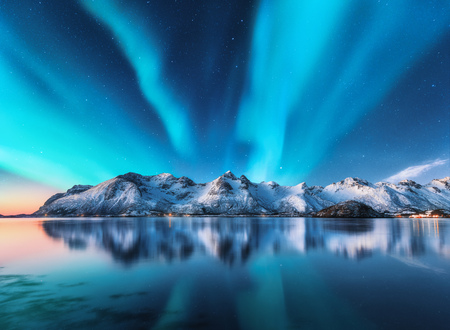 Nordlichter und schneebedeckte Berge auf den Lofoten, Norwegen. Nordlicht. Sternenhimmel mit Polarlichtern und schneebedeckten Felsen, die sich im Wasser widerspiegeln. Nachtwinterlandschaft mit Aurora, Meer. Natur Standard-Bild