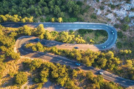 Aerial view of mountain curve road with cars, green forest at sunset in summer in Europe. Landscape with asphalt road, trees on the rocks. Roadway through the park. Top view from flying drone. Nature