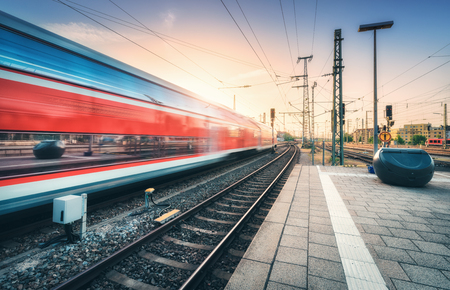 Red high speed train in motion on the railway station at colorful sunset. Blurred modern intercity train with sky reflection in windows on the railway platform. Passenger transportation. Railroad Stock Photo