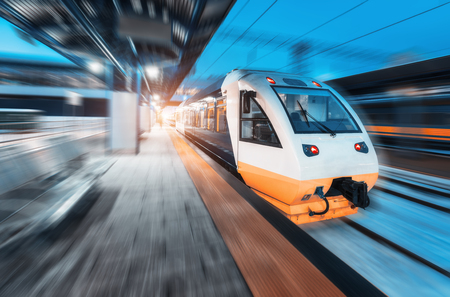 Moving train on the railway station at night. Urban landscape with modern high speed train in motion on the railway platform with illumination at dusk. Intercity vehicle. Passenger railroad travel Banco de Imagens - 118406924