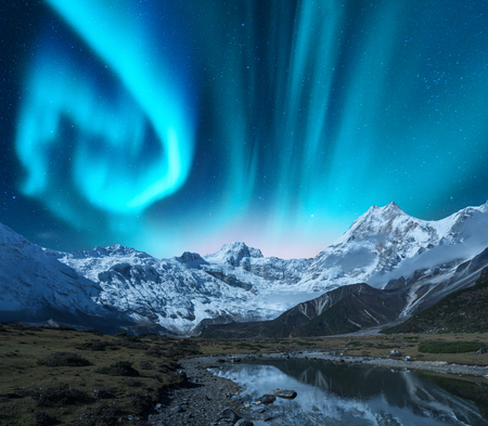 Aurora borealis over the snowy mountains, coast of the lake and reflection in water. Northern lights above snow covered rocks. Winter landscape with polar lights, lake. Starry sky with green aurora
