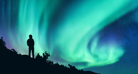 Aurora borealis and silhouette of a woman with backpack at night. Girl on the hill, starry sky with northern lights. Sky with stars and polar lights. Trekking. Landscape with bright aurora and people Imagens
