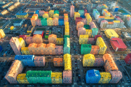 Aerial view of the colorful buildings in european city at sunset. Cityscape with multicolored houses, cars on the street in Kiev, Ukraine. Top view. Urban landscape. Aerial photo of a downtown