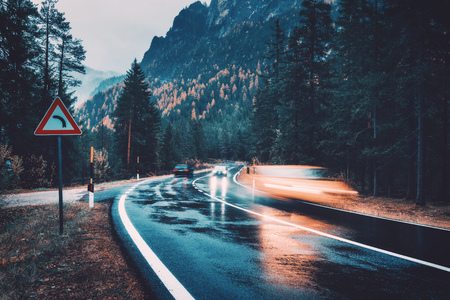 Blurred cars in motion on the road in autumn forest in rain. Perfect asphalt mountain road in overcast rainy day. Roadway, pine trees in italian alps. Transportation. Highway in foggy woodland. Travel