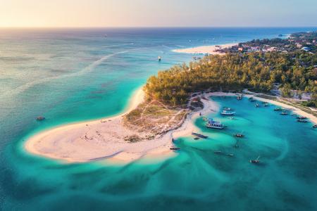 Luftaufnahme der Fischerboote an der tropischen Küste mit Sandstrand bei Sonnenuntergang. Sommerurlaub am Indischen Ozean, Sansibar, Afrika. Landschaft mit Boot, grünen Bäumen, transparentem blauem Wasser. Ansicht von oben