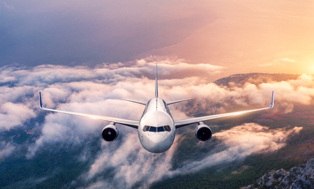 Airplane is flying over clouds at sunset in summer. Landscape with passenger  airplane, low clouds, sea, purple sky at dusk. Front view of the aircraft. Business travel. Commercial plane. Aerial view
