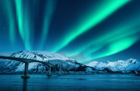 Bridge and aurora borealis over snowy mountains at night in Lofoten islands, Norway. Amazing northern lights and reflection in water. Winter landscape with starry sky, polar lights, road, sea. Space