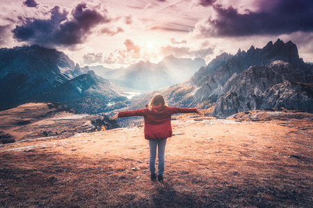 Young woman with raised up arms and mountains at sunset in autumn in Dolomites, Italy. Landscape with happy girl in red jacket, dramatic sky with clouds, orange grass and trees, high rocks in fall Banco de Imagens