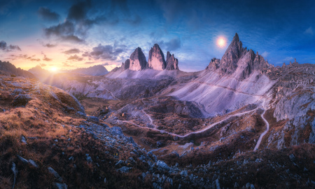 Mountain valley at beautiful sunset. Autumn landscape with mountains, hills, stones, grass, blue sky with clouds and moon at night. High rocks at dusk. Twilight in Tre Cime in Dolomites, Italy. Travel