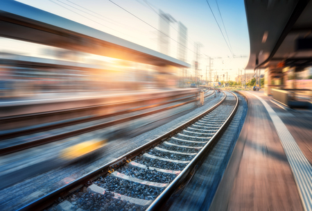 Railway station with motion blur effect at sunset. Industrial landscape with railroad, blurred railway platform, sky with orange sunlight in the evening. Railway junction in Europe. Transportation Banco de Imagens - 120670965