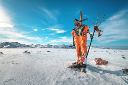 Scarecrow in orange clothes and gas mask with trident is against blue sky with clouds and snowy meadow. Winter landscape with funny dummy, stones in snow and mountains in Teriberka, Russia. Travel