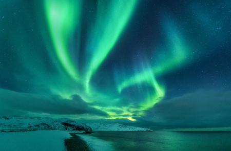 Aurora borealis over ocean. Northern lights in Teriberka, Russia. Starry sky with polar lights and clouds. Night winter landscape with aurora, sea with stones in blurred water, snowy mountains. Travel 免版税图像