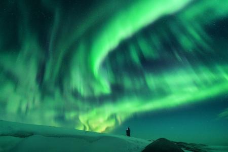 Aurora i sylwetka samotnie stojącego mężczyzny na wzgórzu. Lofoty, Norwegia. Aurora borealis i fotograf. Niebo z gwiazdami i zielonymi światłami polarnymi. Nocny krajobraz z zorzą polarną. Podróż