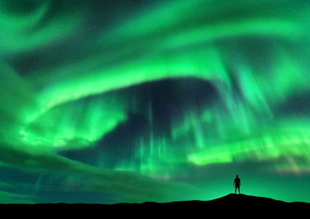 Aurora borealis and silhouette of standing man. Lofoten islands, Norway. Aurora and happy man. Sky with stars and green polar lights. Night landscape with aurora and people. Concept. Travel background 免版税图像
