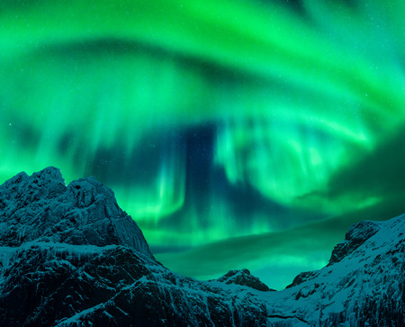 Aurora borealis above the snow covered mountain peak in Lofoten islands, Norway. Northern lights in winter. Night landscape with polar lights, snowy rocks. Starry sky with aurora. Nature background