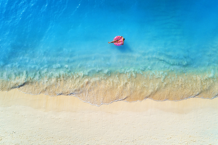 Luftaufnahme einer jungen Frau, die mit dem Donut-Schwimmring im klaren blauen Meer mit Wellen bei Sonnenuntergang im Sommer schwimmt. Tropische Luftlandschaft mit Mädchen, azurblauem Wasser, Sandstrand. Ansicht von oben. Reise