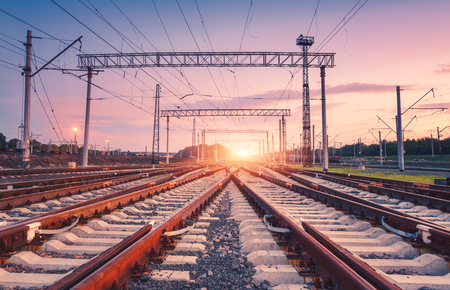 Modern railway station at night in Europe. Industrial landscape with railroad junction, colorful sky at sunset. Railway platform in twilight. Railway background. Heavy industry. Freight transportation