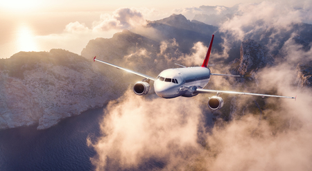 Airplane is flying over mountains and low clouds at sunset in summer. Landscape with passenger airplane, sky in clouds, rocks, sea, sunlight. Business travel. Commercial plane. Aerial view of aircraft 免版税图像