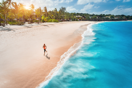 Aerial view of the running young woman on the white sandy beach near sea with waves at sunset. Summer holiday. Top view of sporty slim girl, clear azure water. Indian Ocean. Lifestyle and sport