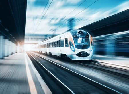 Szybki pociąg na stacji kolejowej o zachodzie słońca w Europie. Nowoczesny pociąg międzymiastowy na peronie kolejowym. Miejska scena z pięknym pociągiem pasażerskim na kolei i budynkach. Krajobraz kolejowy