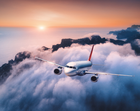 Passenger airplane is flying over clouds at sunset. Landscape with white airplane, low clouds, sea coast, orange sky at dusk. Aircraft is take off. Business trip. Commercial plane. Travel. Aerial view