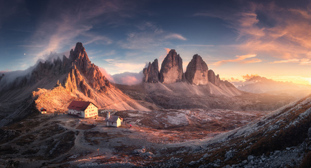 Mountain valley with beautiful house and church at sunset in spring. Landscape with buildings, high rocks, colorful sky, clouds, sunlight. Mountains in Tre Cime park in Dolomites, Italy. Italian alps