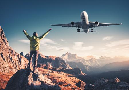 Avión y hombre en la piedra con los brazos levantados contra las montañas al atardecer. Hombre deportivo feliz, avión de pasajeros volando, rocas y cielo azul en Dolomitas, Italia. Avión viajero y aterrizaje Foto de archivo